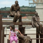 Cute little girl, laughing with the laughing statues
