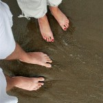 Feet in the Mediterranean Sea. The sand is more coarse, almost like gravel
